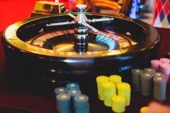 Multicolored casinolijst met roulette in motie met groep gokkende rijke rijke mensen op de achtergrond Royalty-vrije Stock Afbeelding