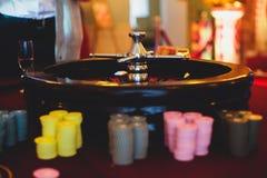 Multicolored casinolijst met roulette in motie met groep gokkende rijke rijke mensen op de achtergrond Royalty-vrije Stock Foto's