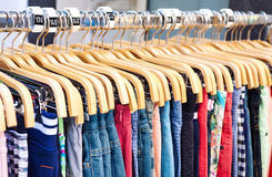 Multicolored casual clothing on wooden hangers stock photos