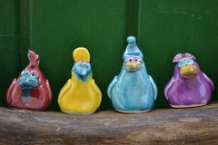 Multicolored ceramic birds on a wooden stand stock image