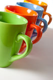 Multicolored ceramic mugs over white Stock Photos