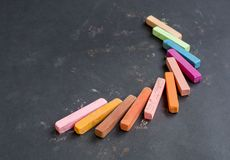 Multicolored chalk on a black background royalty free stock photography