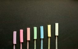 Multicolored chalk on slate stock images