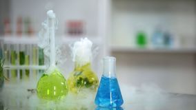 Multicolored chemical liquids in flasks bubbling and emitting smoke, reaction. Stock photo royalty free stock photos