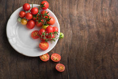 Multicolored cherry tomatoes in white plate on a wooden background, of vegetarian food, vegetables Royalty Free Stock Images