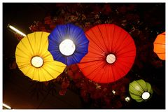 Multicolored Chinese lanterns hanging from the building ceiling with dark background and glowing in the dark night stock photos