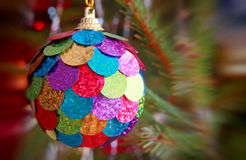 Multicolored Christmas ball on pine branch with soft bokeh. Stock Photos