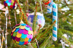 Multicolored Christmas ball and santa cane on pine branch. Stock Photo