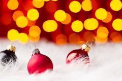 Multicolored christmas balls in white fur colored lights Royalty Free Stock Photos