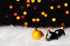 Multicolored christmas balls in white fur colored lights Stock Photos
