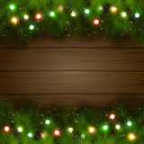 Multicolored Christmas garland. Wooden background with branches of Christmas tree and multicolored light bulbs, illustration Royalty Free Stock Photography