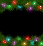 Multicolored Christmas lights on pine branches isolated on black Stock Photos