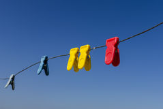 Multicolored clothes clamp. On a wire with sky as background stock photos
