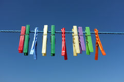 Multicolored clothespin hanged on a blue cord Royalty Free Stock Photography