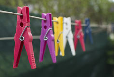Multicolored clothespins on the clothesline. Colorful pegs on the clothesline Stock Photos