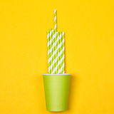 Multicolored cocktail tubes in green paper disposable cup royalty free stock images