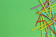 Multicolored cocktail tubes straws on green background stock image