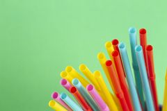 Multicolored cocktail tubes straws on green background royalty free stock photography
