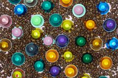 Multicolored coffee pod capsule on coffee beans close up.  royalty free stock image