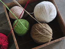 Multicolored coils of thread lie in a wooden box: white wool, green, beige and red. Stock Photography