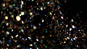 Multicolored confetti particles flying being exploded colorful stars and hearts bouncing slow motion. Multicolored confetti flying after being exploded, colorful stock video