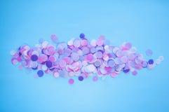 Multicolored confetti and sparkles on blue background. Beautiful colorful confetti and sparkles on blue background stock photos