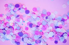 Multicolored confetti and sparkles on pink background. Flat lay of multicolored confetti and sparkles on pink background stock photography