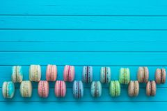 Multicolored cookies macaron or macaroons lie on a wooden turquoise background in checkerboard pattern, top view, copy. Space Royalty Free Stock Photo