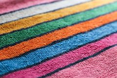 Multicolored cotton terry fabric towel cloth with stripe patern red blue orange yellow white green pink background. Focused Royalty Free Stock Images