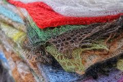 Knitted woolen shawls stacked. Multicolored cozy knitted wool shawls stacked in a pile, close-up royalty free stock photo