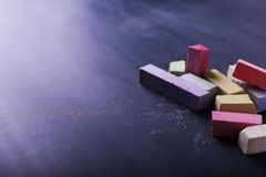 Multicolored crayons lie on a black chalkboard, copy space. The concept of school, education and childhood stock image