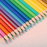 Multicolored crayons on white squared paper background. Stock Image