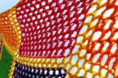 Multicolored crochet blanket. Multicolored crochet blanket on sky background royalty free stock photo