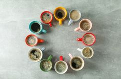 Multicolored cups of coffee circle on grey background, top view. And space for text royalty free stock images