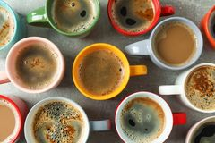 Multicolored cups of coffee on grey table as background. Top view stock photos
