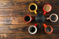 Multicolored cups and coffee maker on wooden background, top view. And space for text stock image