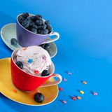 Ice cream with blueberries.  Free space for text. Multicolored cups with ice cream and blueberries on a blue background Stock Photos