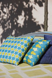 Multicolored cushions in a patio with tree trunk and shadow Royalty Free Stock Photography