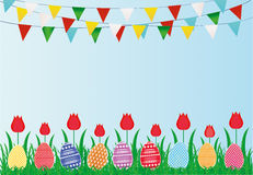 Multicolored decorated Easter eggs on the green grass with flowers. Tulip and a garland of flags. Bunting. Greeting card or invitation for a holiday. Vector Stock Photos
