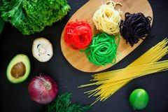 Multicolored deegwaren op houten raad en rauwe groenten op donkere lijst Vlak leg Hoogste mening Stock Fotografie