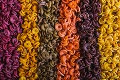 Multicolored deegwaren van ongebruikelijke vorm met natuurlijke plantaardige die kleurstoffen, door strepen worden gescheiden ach stock afbeeldingen