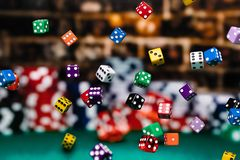 Free Multicolored Dice Chips Cascading In Front Of A Background Of Stacked Poker Chips Stock Photography - 155531512