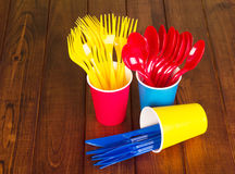 Multicolored, disposable cutlery and glasses on  background of dark wood Royalty Free Stock Photos
