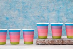 Multicolored disposable paper cups. In row on blue background, abstract concept Royalty Free Stock Photo