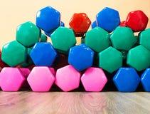 Multicolored domoren in de gymnastiek voor geschiktheid, gewichtsverlies en cardio, close-up, achtergrond stock foto's