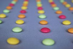 Multicolored dragees arranged in rows. Multicolored dragee arranged in rows on a gray fabric Royalty Free Stock Photography