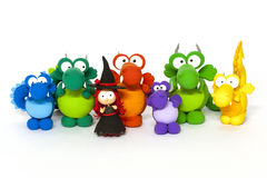 Multicolored dragons and young witch on white. Multicolored handmade modelling clay dragons and red haised young witch on white Stock Photography