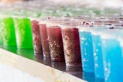 Multicolored dranken in plastic glazen stock foto's