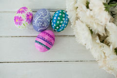 Multicolored Easter eggs and bunch of flower on wooden background Royalty Free Stock Photo