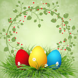 Multicolored easter eggs in green grass. With green frame of leaves Royalty Free Stock Image